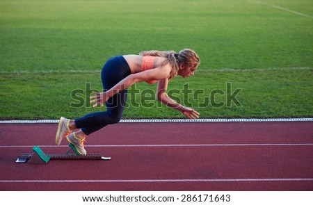 woman  sprinter leaving starting blocks on the athletic  track. Side view. exploding start - stock photo