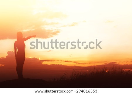 woman standing alone at the field during beautiful sunset - stock photo