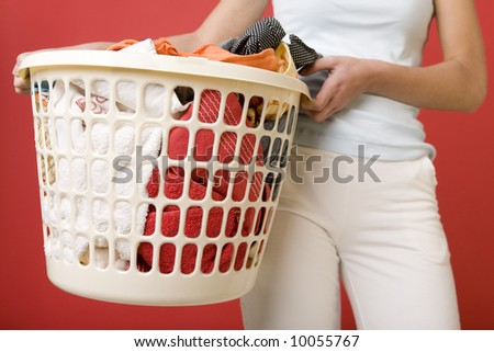 Woman standing and holding in hands full laundry basket. Closeup on basket. Front view. - stock photo