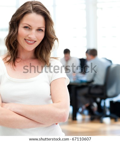 Woman standing at a meeting while her team working in the background - stock photo
