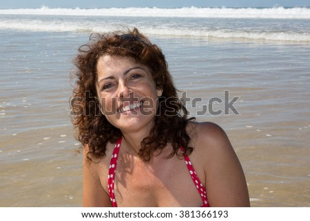 Woman standing at beach smiling at the camera - stock photo