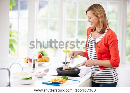Woman Standing At Hob Preparing Meal In Kitchen - stock photo