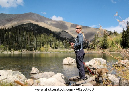 Woman standing at lake with dog - stock photo