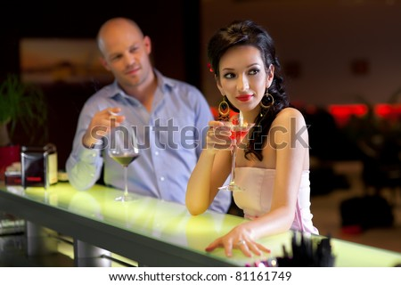woman standing at the bar with men behind, looking at her - stock photo