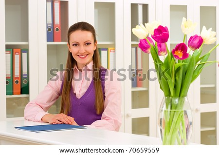 Woman standing at the reception, looking on camera and smiling - stock photo