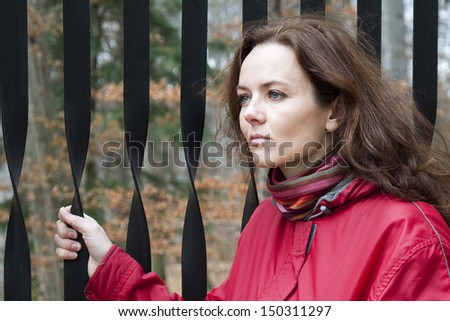 Woman standing by an iron gate. - stock photo