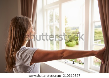 Woman Standing By Bedroom Window And Opening Curtains - stock photo