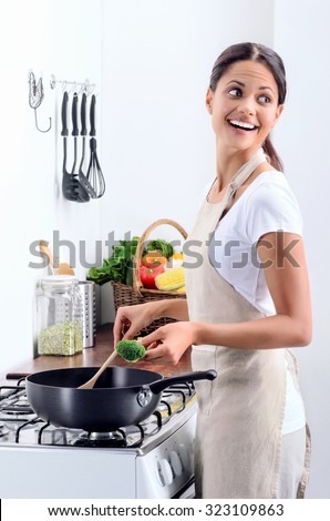 Woman standing by the stove in the kitchen, looking over her shoulder while she stirs and cook  - stock photo