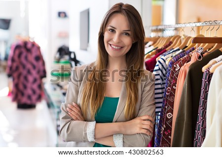 Woman standing in a clothing store  - stock photo