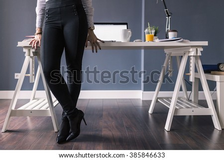Woman standing in front of her desk, only legs in shot.  - stock photo
