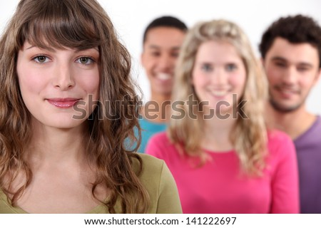 Woman standing in front of her peer group - stock photo