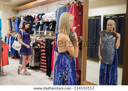 Woman standing in front of mirror holding up shirt in clothing store - stock photo