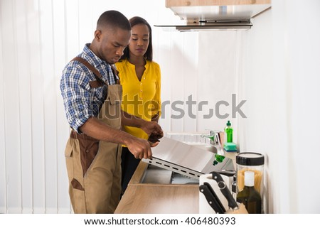 Woman Standing In Front Serviceman Repairing Stove - stock photo