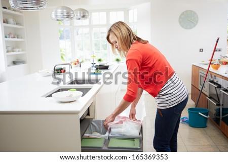 Woman Standing In Kitchen Emptying Waste Bin - stock photo