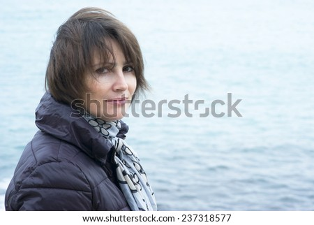 Woman standing in windy conditions in front of the sea - stock photo