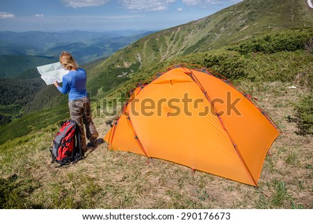 Woman standing near tent and looking at the hike map in the beautiful mountain landscape - stock photo