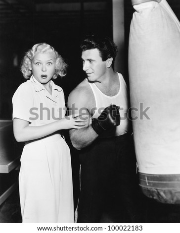 Woman standing next to a boxer feeling his arms and being astonished - stock photo