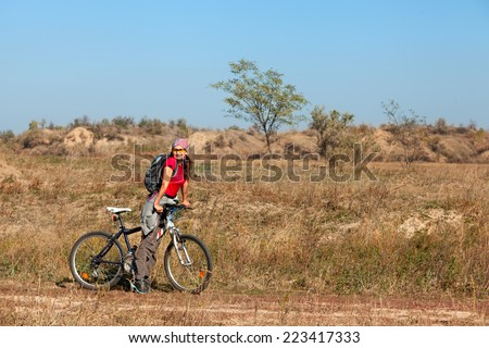 Woman standing next to a mountain bike and looking at the camera and smile - stock photo