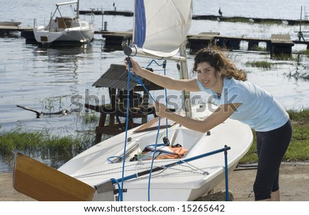Woman standing next to sailboat setting rigging on sails. Looking at camera. Horizontally framed photo - stock photo