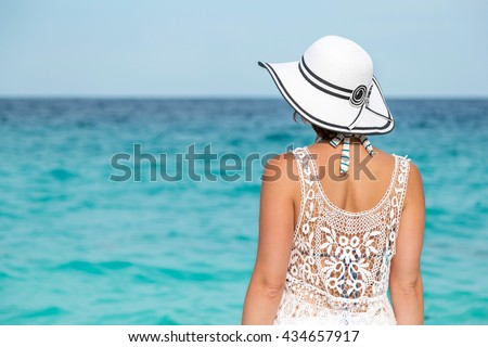 Woman standing on a beach facing away from the camera, looking at marvelous, breathtaking turquoise sea - stock photo