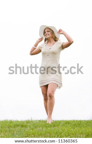 Woman standing on a grassy hill and holding her hat - stock photo