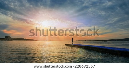 Woman standing on pier near the sea and looking at sunset, tranquil scene. Beautiful seascape. Image with sunlight effect - stock photo