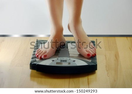 Woman standing on scales - stock photo