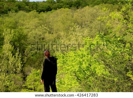 Woman standing on the edge of a bluff enjoying the view of the gorge in front of her; Midwest - stock photo