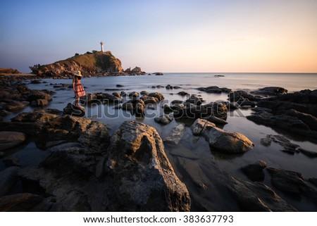 Woman standing on the rock at Lanta island's Lighthouse, Krabi, Thailand - stock photo