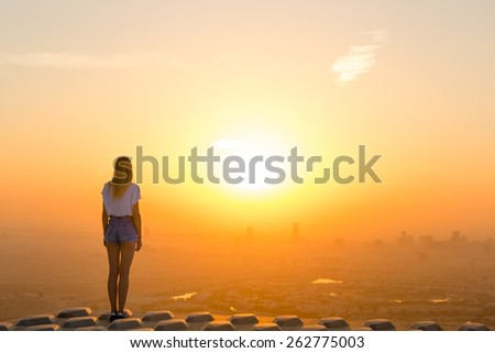 Woman standing on top of skyscraper overlooking the city at sunrise - stock photo