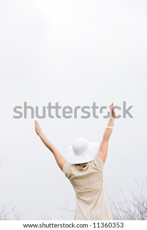 Woman standing outside with her arms up in the air with her back to the camera - stock photo