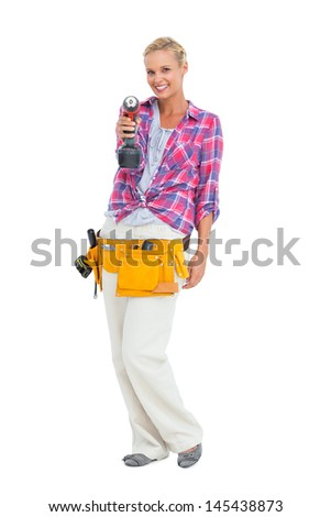 Woman standing while pointing a drill at camera on white background - stock photo