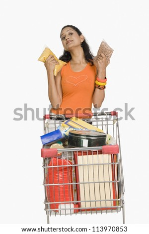 Woman standing with a shopping cart and showing packets - stock photo