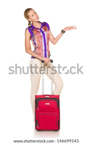Woman standing with red suitcase and showing blank copy space, against white background - stock photo