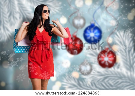 Woman standing with shopping bags against baubles hanging over christmas scene - stock photo