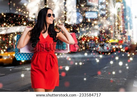 Woman standing with shopping bags against blurry new york street - stock photo