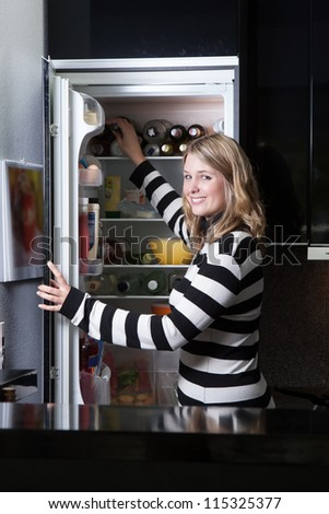 Woman stands in front of the opened fridge in the kitchen - stock photo
