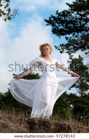 Woman stands near precipice. Wind blows the white dress. - stock photo