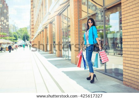 Woman  stands near window shop - Young pretty girl standing in front of a boutique holding shopping paperbags - stock photo