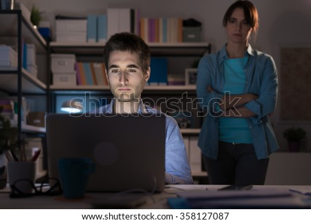 Woman staring at his husband connecting to internet late at night at home, she is disappointed and standing with arms crossed behind him, relationships problems concept - stock photo