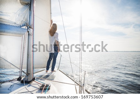 woman staying on the sailboat during sunset - stock photo