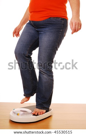 Woman stepping on weighing scales - stock photo