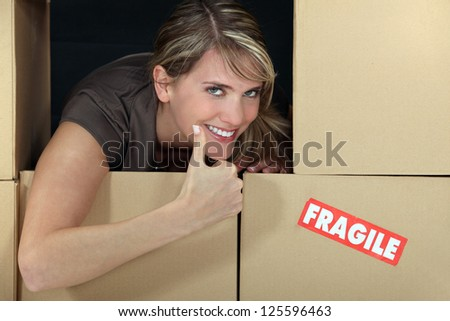Woman stood amongst fragile boxes - stock photo