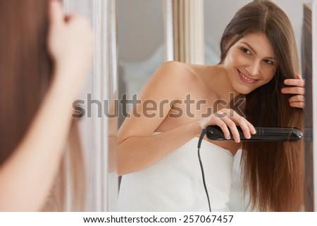 Woman straightening hair with straightener - stock photo