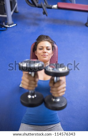 Woman straining to lift weights in gym - stock photo