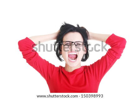 Woman stressed is going crazy pulling her hair in frustration. - stock photo