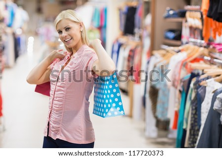 Woman stretching arms with bags - stock photo