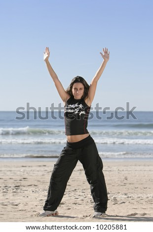 woman stretching at the beach - stock photo