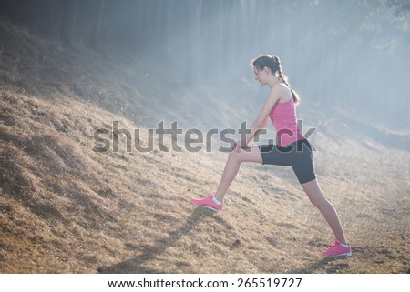 Woman stretching before running in the morning during a sunrise wearing sports wear - stock photo
