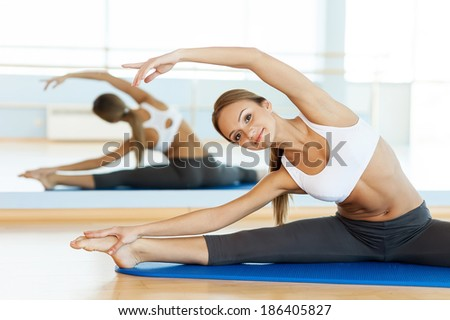 Woman stretching. Cheerful young woman warming up before training - stock photo